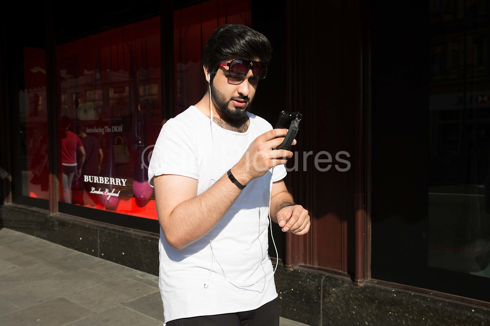 A young man walks along the pavement on Brompton Road looking at his mobile phone on 26th May 2017 in London, United Kingdom. From the series Our Small World, an observation of our mobile phone obsessions