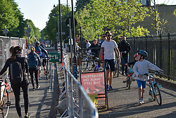 © Licensed to London News Pictures. 26/04/2020. London, UK. Members of the public cross the river at Hammersmith Bridge joining numbers of people making the most of the fine weather on a weekend where the public are urged to observe social distancing and only leave home where absolutely necessary.  Photo credit: Guilhem Baker/LNP