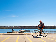 19 APRIL 2020 - DES MOINES, IOWA: A person rides his bike around Gray's Lake, a popular public park and lake south of downtown Des Moines. After a week of colder than normal weather, including three inches of snow, the weekend was spring like and people went to public parks to enjoy the pleasant weather.      PHOTO BY JACK KURTZ