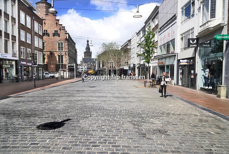 Nederland, Nijmegen, 30-4-2020  De binnenstad van Nijmegen . Het is duidelijk rustiger en stiller als normaal in de straten, winkelstraten van het centrum in de stad . Mensen blijven thuis om zo min mogelijk risico te nemen ivm het corona virus . Terrassen zijn gesloten . Stadsbeeld van een winkelstraat in het centrum van de stad . Nu de drukte toeneemt vanwege het mooie weer en het langdurige thuisblijven, binnenzitten, is het straatbeeld drukker . Foto: Flip Franssen