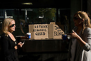 Two women drink Cafe Nero coffees during a corporate greed and austerity measure protest that took place around the world.