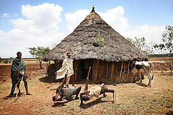 The groomsmen for Alelegn Challe, 23, dance outside the hut where he was waiting for his bride, Leyualem Mucha, 14, in the Amhara Region, Ethiopia on May 23, 2007.  Leyualem had never met her husband before her wedding day, yet sumitted as they bound her in the white wedding cloth. The men later said it was placed over her head so she would not be able to find her way back home, should she want to escape the marriage.