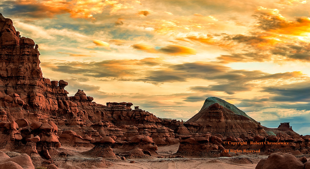 Surrealistic Third Valley: Exposed rock cliffs and hoodoos, with boulders held on high provide a surrealistic setting under an equally unnatural sunset over the Third Valley - Goblin State Park, Utah USA.