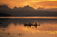 Two people paddle a tandem sea kayak in Khao Sok National Park, Thailand.