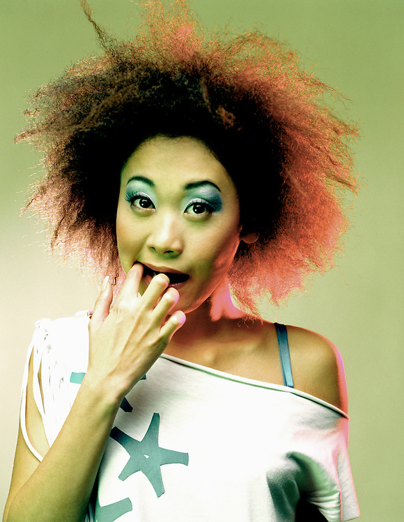 Colour studio portrait of funky asian girl with afro hair and with finger in her mouth