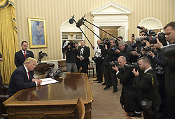 President Donald Trump signs his first executive order as president, ordering federal agencies to ease the burden of President Barack Obama's Affordable Care Act, in the Oval Office at the White House in Washington, D.C. on January 20, 2017. Photo by Kevin Dietsch/UPI