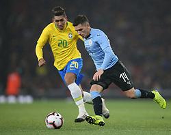 Brazil's Roberto Firmino and Uruguay's Lucas Torreira battle for the ball