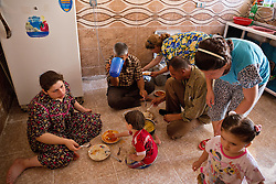 © Licensed to London News Pictures. Hamdaniyah, Iraq. 26/07/2014. Christian refugee Ra'id Samir Kamal, 45 (R kneeling), formerly a driver in Mosul, east lunch with some of the members of his extended family in the partially built house they inhabit in Hamdaniyah, Iraq. Samir left Mosul on Friday the 18th of July when Islamic State fighters issued an ultimatum to the city's Christian community. When the family left they were forced to pay a tax for their car, their son (19) was threatened at knifepoint to ensure they handed over all of their possessions including family photographs.<br /> <br /> Having taken over Mosul Iraq's second largest city in June 2014, fighter of the Islamic State (formerly known as ISIS) have systematically expelled the cities Christian population. Despite having been present in the city for more than 1600 years, Christians in the city were given just days to either convert to Islam, pay a tax for being Christian or leave; many of those that left were also robbed at gunpoint as they passed through Islamic State checkpoints.. Photo credit : Matt Cetti-Roberts/LNP