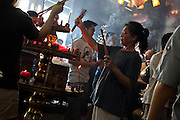In a buddhist temple in Georgetown on island of Penang, Malaysia, people burn incense and prepare offerings.
