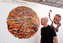 © Licensed to London News Pictures. 05/06/2015. Bristol, UK.  The Other Art Fair comes to the Arnolfini Gallery in Bristol.  Picture of Steve McGinn with his work.  As the UK's leading artist fair, The Other Art Fair gives art lovers the unique opportunity to buy directly from 70 of the best emerging and undiscovered artists.  Photo credit : Simon Chapman/LNP