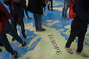 The legs and feet of foreign students standing over Europe on a map of the world at the National Maritime Museum, Greenwich.