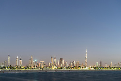 Skyline at dusk of skyscrapers and Burj Khalifa along Sheikh Zayed Road from Jumeira Open Beach in Dubai United Arab Emirates