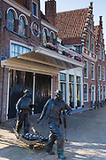 Bronze statue cheese porters / carriers in Kaasmarkt cheese market, Kaasmarkten in Edam, The Netherlands