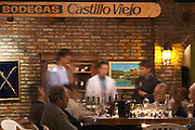 The winemaker and oenologist and a group of wine tasters tasting in the cellar. A sign on the wall saying Bodegas Castillo Viejo. Bodega Castillo Viejo Winery, Las Piedras, Canelones, Uruguay, South America