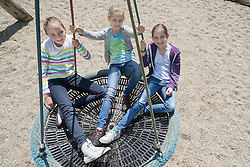 High angle view of girls swinging on a swing in playground, Munich, Bavaria, Germany