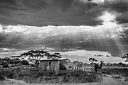 A black and white image of a traditional Maasai village beneath a cloudy, story sky ,Amboseli, Kenya, Africa