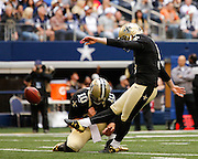 New Orleans Saints quarterback Chase Daniel (10) holds the ball as kicker Garrett Hartley (5) kicks an extra point against the Dallas Cowboys at Cowboys Stadium in Arlington, Texas, on December 23, 2012.  (Stan Olszewski/The Dallas Morning News)