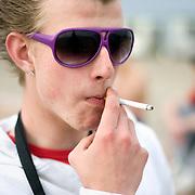 Nederland Rotterdam 19 april 2009 20090419 Foto: David Rozing ..Jongen rookt sigaretje op strandje Nesselande, zomerse kleding, grote zonnebril, mode, trends, trend..Foto: David Rozing/