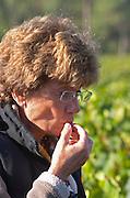 Tasting a grape to test ripeness. Martine Cazeneuve, owner. Merlot. Chateau Paloumey, Haut Medoc, Bordeaux, France.