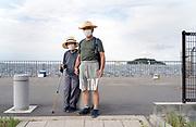 elderly woman walking with son portrait and Sarushima Island Yokosuka in the background