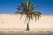 A man walks carrying a suitcase under a large palm tree down a street in Meknes, Morocco.