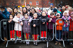 © Licensed to London News Pictures . 26/01/2020. Manchester, UK. Children lean on fencing to watch a stage in China Town . Thousands of people watch a display of oriental culture and a procession through Manchester city centre to mark Chinese New Year . Photo credit: Joel Goodman/LNP