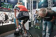 Een man kijkt op de fietsbeurs BikeMotion in de Jaarbeurs in Utrecht naar de fiets waarop een meisje een virtueel parcours aflegt.<br /> <br /> A man is looking at a racing bike, while a girl is riding at it at trade fair BikeMotion in Utrecht.