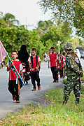 "Sept. 27, 2009 -- PATTANI, THAILAND: Thai soldiers provide security for children walking to the Gahong School in Pattani, Thailand, Sept 27. Schools and school teachers have been frequent targets of Muslim insurgents in southern Thailand and the army now provides security at many government schools.  Thailand's three southern most provinces; Yala, Pattani and Narathiwat are often called ""restive"" and a decades long Muslim insurgency has gained traction recently. Nearly 4,000 people have been killed since 2004. The three southern provinces are under emergency control and there are more than 60,000 Thai military, police and paramilitary militia forces trying to keep the peace battling insurgents who favor car bombs and assassination.  Photo by Jack Kurtz"