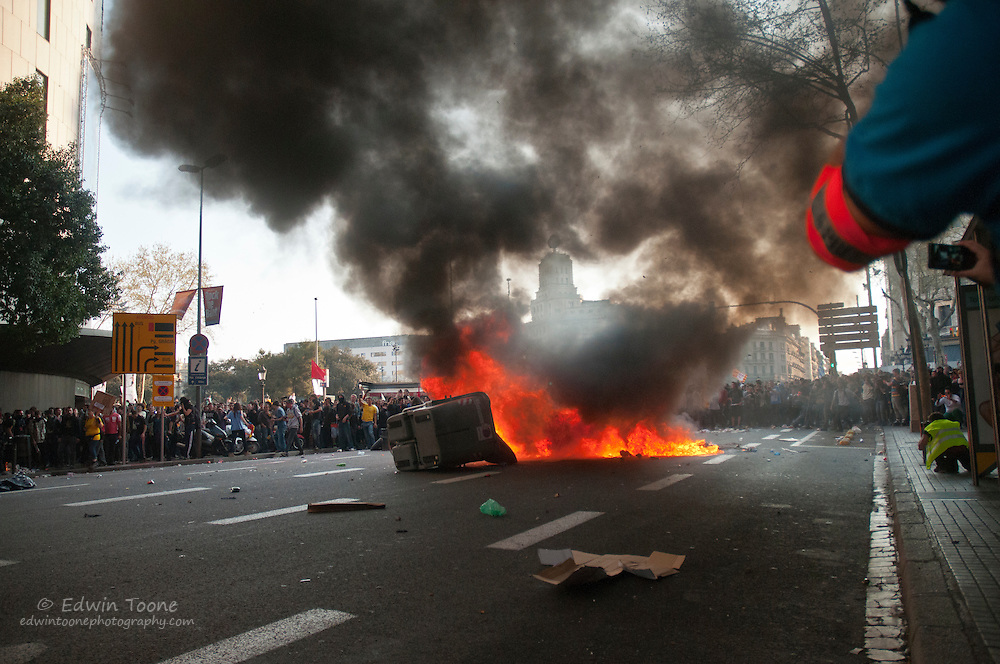 A battle for ground begins as rioters push the police back and set fire to a garbage container.