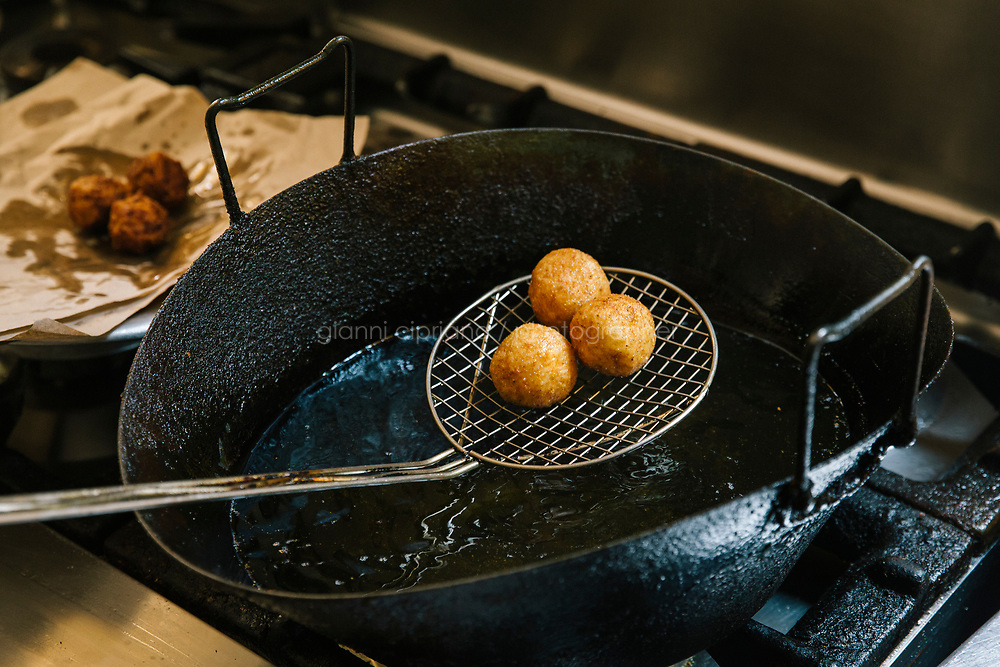 NAPLES, ITALY - 1 AUGUST 2018: Arancinas (fried rice balls) are fried here at Cantina del Gallo, a family-owned restaurant in the Rione Sanità in Naples, Italy, on August 1st 2018.<br /> <br /> Cantina del Gallo, in the Rione Sanità, was established in 1898 and run by four generations of the Silvestri family. The cantina began as a store selling bulk wine and oil. It was only in the 1950s, when the legendary Aunt Cuncetta began cooking, that it became the simple and genuine tavern it is today.<br /> There are three dishes that are the restaurant's workhorses, and the ones we always seem to rotate between: the pennette alla sorrentina (a variation of the classic gnocchi alla sorrentina, seasoned with tomato, basil and stringy mozzarella), the baked cod (although the fried cod is just as mouth-watering) and the pizza cafona (peasant pizza), topped with oregano, cheese, chile and with double the tomatoes (tomato juice and chopped tomatoes).