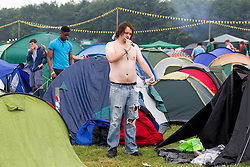 © Licensed to London News Pictures . 24/08/2012 . Leeds , UK . A camper freshening up after a night in his tent at the Leeds festival , in Bramham Park . Photo credit : Joel Goodman/LNP