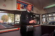 A 1990s bus conductor looks back along his bus during his shift on board of a red London Routemaster bus, on 18th February 1992, in London, England.