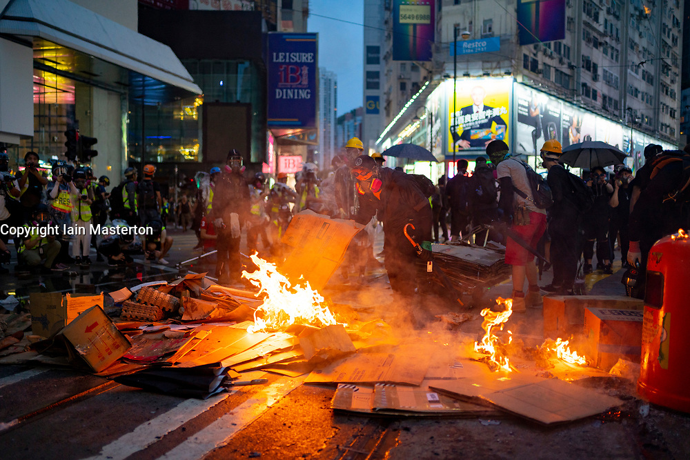 Hong Kong. 6 October 2019. Tens of thousands of pro-democracy protestors march in pouring rain through centre of Hong Kong today from Causeway Bay to Central. Peaceful march later turned violent as a hard-core of protestors confronted police. Pic; Fires set on streets of Causeway Bay.  Iain Masterton/Alamy Live News.