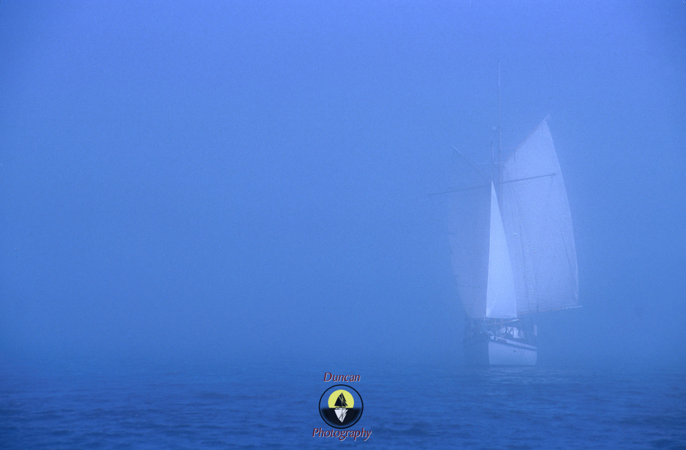 A square-rigged schooner comes into Lunenburg, NS, Canada from the out in the fog. In the age of sail, The Flying Dutchman was a legendary ghost ship which would be seen by sailors in the fog prior to a disaster.  Photo by Roger S. Duncan.