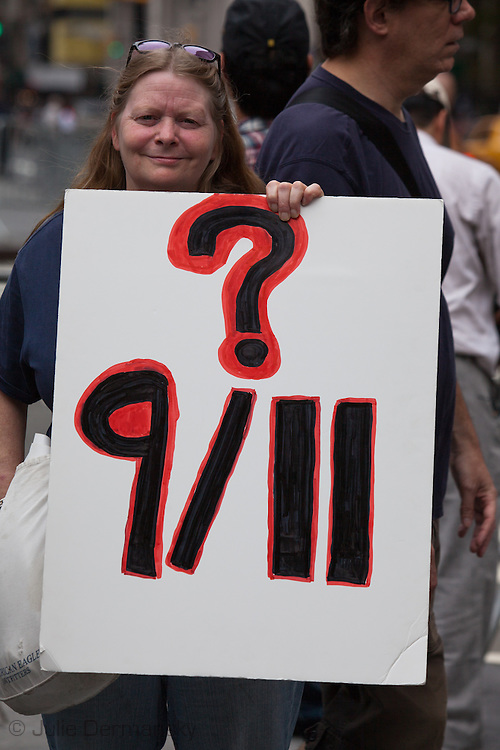 Lauri Robinson  holds up a  question 9/11 sign at a rally to find out the truth about September 11th held on 10th anniversary of the 9/11 attacks on the World Trade Center towers across from St Paul's Chapel near ground zero. The 9/11 Truth Movement started in 2006 by family members who want answers about what happened on 9/11and have staged rallies at Ground Zero every year on 9/11.