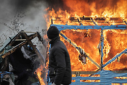 © Licensed to London News Pictures. Calais, France. 02/03/16. A refugee walks past a burning shelter, set alight to protest the demolition of the Calais 'Jungle' refugee camp. French authorities have begun clearing the southern half of the camp, which charities estimate to contain some 3,500 people hoping to reach the United Kingdo. Photo credit: Rob Pinney/LNP