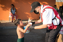 A Major from the Mexican Salvation Army hands a cream bun and hot chocolate to one of hundreds of children they feed twice a week in a camp of asylum seekers in Tijuana, Mexico.