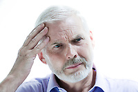 portrait on isolated withe background of a handsome expressive senior holding his head in hand headache memory loss migraine