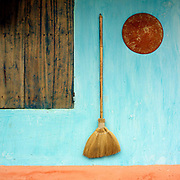 A traditional broom and a conical hat hanging on a blue painted wall of a house in Yen Lu commune, Bac Giang province, Vietnam.