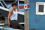 """A North Korean sailor on a boat with a national flag in the town of Sinuiju July 8, 2006. China and North Korea are separated by the Yalu River, upon which Chinese tourists take pleaure cruises across the water to  observe their less economically developed neighbors.  North Korea has threatened to take """"stronger physical actions"""" after Japan imposed punitive measures in response to its barrage of missile tests and pushed for international sanctions. North Korea has vowed to carry out more launches and has said it will use force if the international community tries to stop it. DPRK, north korea, china, dandong, border, liaoning, democratic, people's, rebiblic, of, korea, nuclear, test, rice, japan, arms, race, weapons, stalinist, communist, kin jong il"""