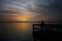 Sunset over Fisherman Pier at Sanibel Lighthouse Point, Mother teach the art of fishing to son while enjoing the beautiful sunset.