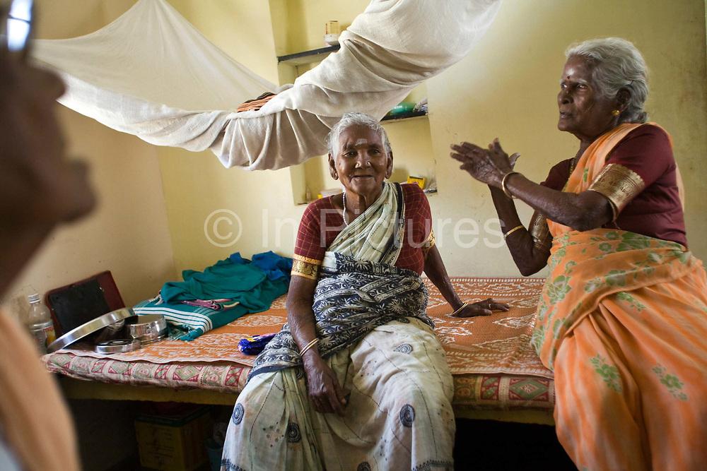 Amaravathy and Jayamal talk to their friends inside their cottage in the Tamaraikulum Elders village, Tamil Nadu, India