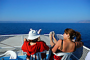 Two mature women sitting at bow of boat, islands in background. Makarska, Croatia