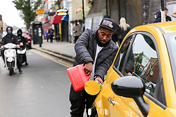 © Licensed to London News Pictures. 25/09/2021. London, UK. A motorist with a petrol can fills his car in the middle of Green Lanes in Haringey in north London as drivers continue to panic buy petrol amid a fuel shortage fear arising from a shortage of HGV drivers.. Photo credit: Dinendra Haria/LNP