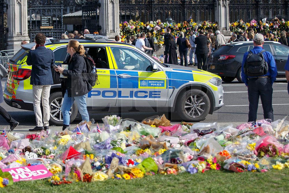 © Licensed to London News Pictures. 27/03/2017. London, UK. A police car patrols in Westminster whilst members of public pay their respects to the victims of Westminster terror attack in Parliament Square, London on Monday, 27 March 2017. Photo credit: Tolga Akmen/LNP