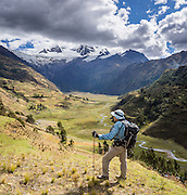 From Pishgopampa village in Jancapampa Valley, a trekker admires 6000-meter peaks of Nevados Pucajirca. Day 4 of 10 days around Alpamayo, in Huascaran National Park (UNESCO World Heritage Site), Cordillera Blanca, Andes Mountains, Peru, South America. This vertical panorama was stitched from 3 overlapping photos.