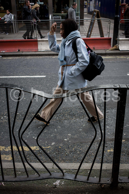 Woman pedestrian walks past bent railings in a London street. In a perfectly-timed picture, the lady strides past the damaged railings, twisted by a vehicle, perhaps - or by someone with strong tools. Her legs are perfectly aligned with the angle of bent steel uprights - now reshaped into diagonals. The street is underoing massive change due to the capital's Crossrail project where pedestrian disruption actually encourages people to walk a shorter route in the road, rather than the safer pavement.