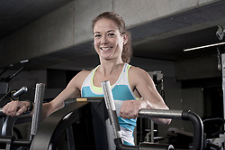 Portrait of a mid adult woman doing exercise on exercise machine in the gym, Bavaria, Germany