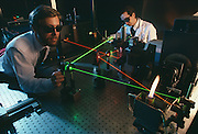 Researchers at the GM tech Center pass multiple lasers through a flame to analyze emissions pollution.