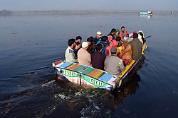 A Kashmiri man ferries  his boat along with the customers across Dal lake on a sunny day in Srinagar, the summer capital of Indian controlled Kashmie, India, Friday 16 November 2018. (Masrat Zahra/ZUMA Press)